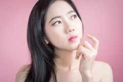 Long hair asian young beautiful woman cross arm and point finger upward isolated over pink background. natural makeup, SPA therapy Royalty Free Stock Image