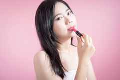 Long hair asian young beautiful woman lipstick, isolated over pink background. natural makeup, skincare, cosmetology and plastic. Royalty Free Stock Images