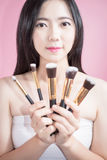 Long hair asian young beautiful woman smile and fun, touch her face and hold cosmetic powder brush set, isolated over pink. Long hair asian young beautiful Royalty Free Stock Images