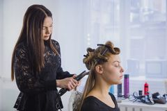 Long hair being straightened with iron by stylist Royalty Free Stock Photography
