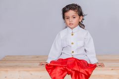 Long hair boy dressed in Thai traditional costume. White shirt with long sleeves, red pants standing on a wooden table stock photo