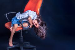 Long hair boy sitting on orange chair. A long hair boy sitting on orange chair in black scene in studio to shoot the children& x27;s fashion stock images