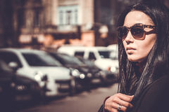 Long hair brunette girl outdoor with city street on background Royalty Free Stock Image