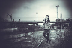Long hair brunette girl outdoor with old industrial bridge behin Royalty Free Stock Photography