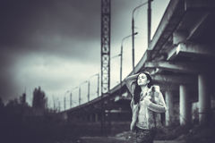 Long hair brunette girl outdoor with old industrial bridge behin Stock Photo