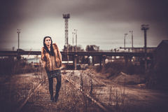 Long hair brunette girl outdoor with old industrial view behind, grain effect Stock Photo