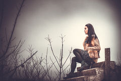Long hair brunette girl outdoor with old industrial view behind, grain effect Stock Image
