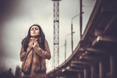 Long hair brunette girl outdoor with old industrial view behind, grain effect Royalty Free Stock Photography