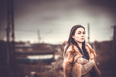 Long hair brunette girl outdoor with old industrial view behind, grain effect Stock Photography