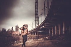 Long hair brunette girl outdoor with old industrial view behind, grain effect Royalty Free Stock Photo