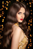 Long hair. Brunette girl with shiny wavy hairstyle and red lips. Makeup. Elegant lady posing in golden dress over Christmas party light background. glamour Stock Photos