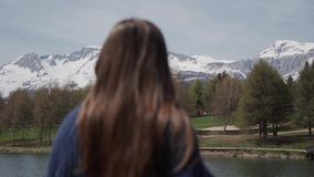 Long-hair brunette woman standing and looking scenic view of mountain lake in Switzerland. Rear view. Floating focus. Close up 4k stock video