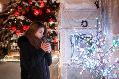 Long hair girl on European Christmas Market. Young woman Enjoying Winter Holiday Season. Blurred Lights background, dusk. Cups wi. Long hair girl on European royalty free stock images