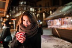 Long hair girl on European Christmas Market. Young woman Enjoying Winter Holiday Season. Blurred  Lights background, dusk. Cups wi Stock Photo