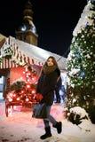 Long hair girl on European Christmas Market. Young woman Enjoying Winter Holiday Season. Blurred Lights background, dusk. Cups wi. Long hair girl on European stock image