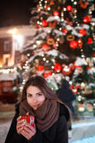Long hair girl on European Christmas Market. Young woman Enjoying Winter Holiday Season. Blurred  Lights background, dusk. Cups wi Stock Photos