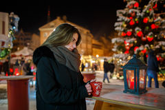 Long hair girl on European Christmas Market. Young woman Enjoying Winter Holiday Season. Blurred  Lights background, dusk. Cups wi Stock Photography