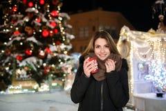 Long hair girl on European Christmas Market. Young woman Enjoying Winter Holiday Season. Blurred Lights background, dusk. Cups wi. Long hair girl on European royalty free stock photos