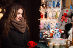 Long hair girl on European Christmas Market. Young woman Enjoying Winter Holiday Season. Handmade knitted toys, crocheted Royalty Free Stock Image
