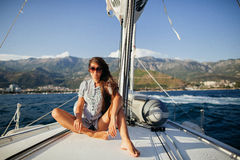 Long hair girl in fashion jeans shirts on yacht in Montenegro Stock Image