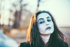 Long hair girl with scary makeup in the forest Stock Photos