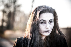 Long hair girl with scary makeup in the forest Royalty Free Stock Photography