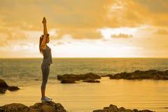 Long hair, good shape Asian woman playing yoga, exercise on rock Stock Photography
