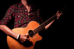 Long hair guy playing guitar acoustic. On studio Royalty Free Stock Photography