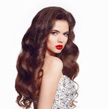 Long hair. Makeup. Beautiful girl portrait. Brunette fashion wom. An with red lips and healthy wavy shiny hairstyle posing isolated on white studio background Stock Photos