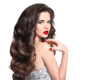 Long hair. Makeup. Beautiful girl portrait. Brunette fashion wom. An with red lips and healthy wavy shiny hairstyle posing isolated on white studio background Royalty Free Stock Photography