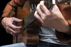 Long hair male guitarist playing with acoustic guitar in leather Royalty Free Stock Photos