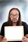 Long Hair Man Holding Small Blank White Board. Close up Serious Adult Man with Long Hair, Wearing Eyeglasses, Holding Small Blank White Board, Emphasizing Copy Stock Photo