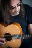 Long Hair Man with Sunglasses Playing a Guitar. Close up Serious Long Hair Man with Sunglasses, Wearing Black Casual Shirt, Playing a Song using a Guitar Royalty Free Stock Photography