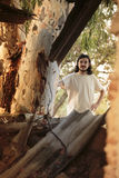 Long Hair Man in White Behind the Tree Stock Image