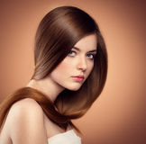 Long hair model. Gentle teenage girl showing her healthy long straight hair. Beautiful Caucasian female model with perfect glossy hair posing in studio Stock Images