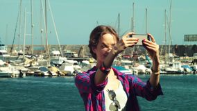 Long hair model take selfie video photo a front of yacht club stock video
