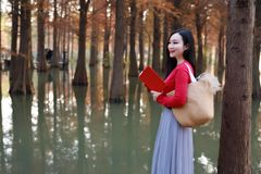 Young asian chinese woman reading in the autumn Water red forest. stock photo