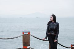Young asian chinese woman Listen to the voice of the sea. Long hair romantic woman relax sit and Listen to the voice of the sea at seaside, xiamen city, fujian royalty free stock image