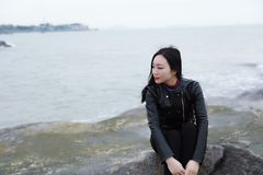 Young asian chinese woman sit on rock of sea , Listen to the voice of the sea. Long hair romantic woman relax sit on rock and Listen to the voice of the sea at royalty free stock image