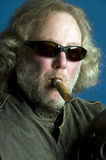 Long hair senior smoking cigar Royalty Free Stock Images