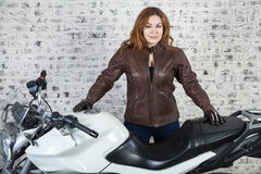 Long hair woman a motorbiker standing near her street motorbike in garage, brick wall background Stock Photography