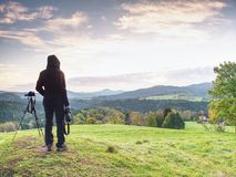Long hair woman photographer stand on meadow and wait for sunrise. Short  grass and  misty and light fog above valley. Minute to sunrise Royalty Free Stock Photo