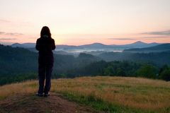 Long hair woman stand on meadow with golden stalks of grass and waiting for sunrise Royalty Free Stock Photo