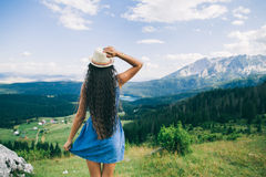 Long hair woman travel in mountains landscape back view Stock Image