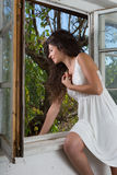Long hair woman in window Royalty Free Stock Photos