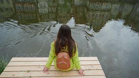 Long-hair woman in yellow jacket with backpack sits on wooden pier at river or pond and looks ducks swim. Traditional. German half-timbered houses are reflected stock video