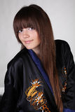 Long hair, young woman in black oriental robe Stock Photo