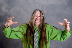Long haired, angry man in green shirt pink glasses Royalty Free Stock Photo