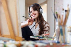 Long-haired  artist  in headphones paints picture Royalty Free Stock Photos