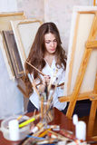 Long-haired  artist paints on canvas Royalty Free Stock Photography